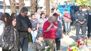 Mourners attend a vigil held in honor of Pomona Police Officer Gregg Casillas, who was killed, and a wounded officer who is recovering in the hospital. (Credit: KTLA)