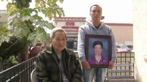 Bi Xu Chen's son hold a photo of the hit-and-run victim while her husband watches on on April 5, 2018. (Credit: KTLA)
