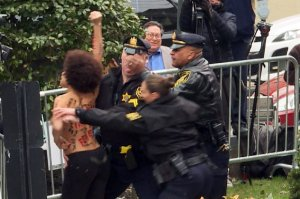 In these video framegrabs from AFP TV, sheriff's officers detain a protester interrupting the arrival of Bill Cosby for the first day of his second trial for sexual assault case at the Montgomery County Courthouse in Norristown, Pennsylvania on April 9, 2018. (Credit: Diane Desobeau/AFP/Getty Images)