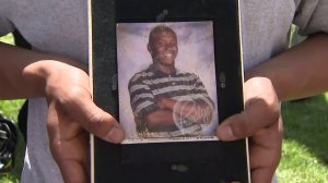 Frederick Frazier is seen in a photo held by a mourner at a vigil for him in South L.A. on April 11, 2018. (Credit: KTLA)
