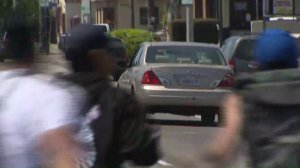 A gold Toyota Avalon flees after striking a pedestrian in South L.A. at a vigil for a cyclist on April 11, 2018. (Credit: KTLA)