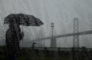 A pedestrian carries an umbrella while walking near the Bay Bridge on February 6, 2014 in San Francisco. (Credit: Justin Sullivan/Getty Images)