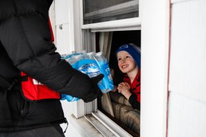Jake McSigue, 6, of Linden, receives a package of bottled water through the window of his grandma's home in Flint, Michigan, on Jan. 21, 2016. (Credit: Sarah Rice / Getty Images)
