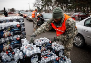 Army National Guard Specialist David Brown loads bottled water into waiting cars at a fire station on Jan. 21, 2016 in Flint, Michigan. (Credit: Sarah Rice / Getty Images)