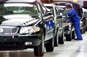 This file photo shows a worker looking at a side mirror of a car at the assembly line of General Motors Company in Shanghai. (Credit: LIU JIN/AFP/Getty Images)