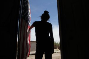 A U.S. flag hangs from the door of the house of a Mexican woman who looks toward the border line between Mexico and the United States in Ciudad Juarez, Mexico, on April 6, 2018. (Credit: Herika Martinez / AFP / Getty Images)