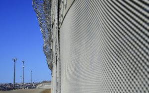 Barbed wire fencing runs across the top of the steel structure in the Border Infrastructure System  in San Diego on April 17, 2018. (Credit:  FREDERIC J. BROWN/AFP/Getty Images)
