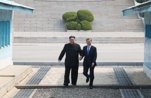 North Korea's leader Kim Jong Un, left, steps with South Korea's President Moon Jae-in across the Military Demarcation Line that divides their countries ahead of their meeting at Panmunjom on April 27, 2018. (Credit: Korea Summit Press Pool / AFP / Getty Images)