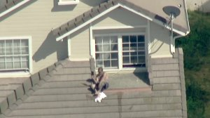 A man sits on top of a home in Hacienda Heights during a standoff with law enforcement on April 24, 2018. (Credit: KTLA)