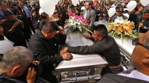 The brothers of Santos Hilario Garcia grieve during funeral services at Our Lady of Guadalupe Church in Delano for Garcia and Marcelina Garcia Perfecto, who were killed when their car overturned while fleeing federal immigration agents. (Credit: Al Seib / Los Angeles Times)