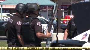 SWAT officers with Anaheim police help search for a man wanted on suspicion of assaulting an officer on April 17, 2018. (Credit: KTLA)
