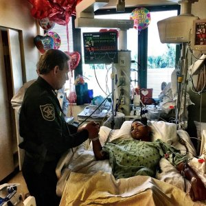 Sheriff Scott Israel holds the hand of Anthony Borge, a student who shot five times in the massacre. (Credit: Broward County Sheriff's Office)