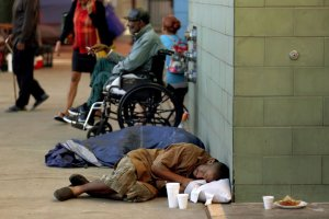 A man sleeps on the sidewalk in front of the Union Rescue Mission in the skid row neighborhood of Los Angeles. (Credit: Francine Orr / Los Angeles Times)