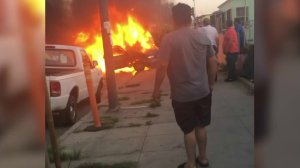 Bystanders watch a vehicle in flames following a crash in South L.A. on April 28, 2018.(Credit: Nora Castillo)