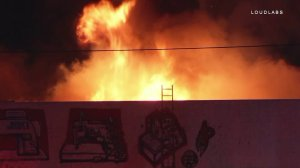 Flames are seen at a fabric business in South L.A. on April 21, 2018. (Credit: Loudlabs/KTLA)