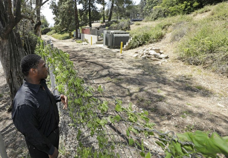 Matthew Whitaker looks at the spot (to the right of the pile of rocks) where he was abandoned as a newborn in brush near a trail in Altadena 20 years ago. (Credit: Myung J. Chun / Los Angeles Times)