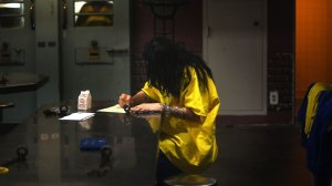 A inmate is seen writing at the Century Regional Detention Facility in Los Angeles in 2017. The jail has been the site of multiple alleged sexual assaults by L.A. County Sheriff's Deputy Giancarlo Scotti, who was arrested in 2017. (Credit: Christina House / Los Angeles Times)
