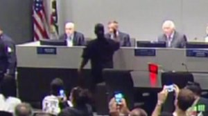 Sheila Brim-Hines is seen tossing the ashes of her niece Wakiesha Wilson, who died in police custody, at Los Angeles Police Chief Charlie Beck at a police commission meeting on May 8, 2018, in a still from footage of the meeting.