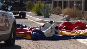 A deflated bounce house sits on the side of a roadway in Victorville after being blown by strong winds onto Highway 395 with a 9-year-old child inside on May 12, 2018. The child was left with minor injuries. (Credit: Loudlabs)