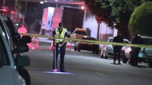 An investigator looks through the scene in South L.A. where a 3-year-old child was struck by a vehicle on May 20, 2018. (Credit: KTLA)