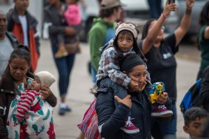 Women and children who are part of a caravan of Central Americans traveling across Mexico walk from Mexico to the U.S. side of the border to ask authorities for asylum on April 29, 2018 in Tijuana. (Credit: David McNew/Getty Images)