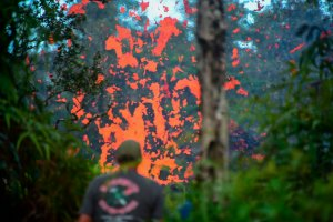 A man watches as lava is seen coming from a fissure in Leilani Estates subdivision on Hawaii's Big Island on May 4, 2018. Up to 10,000 people have been asked to leave their homes on Hawaii's Big Island following the eruption of the Kilauea volcano that came after a series of recent earthquakes. (Credit: FREDERIC J. BROWN/AFP/Getty Images)