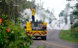 A firefighter takes photos near steam rising from a fissure in Leilani Estates subdivision on Hawaii's Big Island on May 4, 2018. (Credit: FREDERIC J. BROWN/AFP/Getty Images)