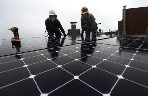 Luminalt solar installers Pam Quan, left, and Walter Morales, right, install solar panels on the roof of a home on May 9, 2018, in San Francisco. (Credit: Justin Sullivan / Getty Images)