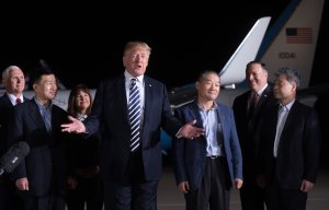 President Donald Trump gestures as he speaks upon the return of U.S. detainees Tony Kim (front Left), Kim Hak-song (right) and Kim Dong-chul (3rd right) after they were released by North Korea, at Joint Base Andrews in Maryland on May 10, 2018. (Credit: Saul Loeb/AFP/Getty Images)