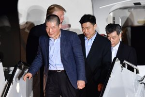 US President Donald Trump (back L) welcomes the arrival of US detainees Kim Dong-chul (L), Kim Hak-song (R) and Tony Kim (2nd R) after they were released by North Korea, at Joint Base Andrews in Maryland on May 10, 2018. (Credit: NICHOLAS KAMM/AFP/Getty Images)