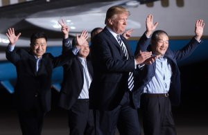 US President Donald Trump (2nd R) walks with US detainees Tony Kim (L), Kim Hak-song (2nd L) and Kim Dong-chul (R) upon their return after they were released by North Korea, at Joint Base Andrews in Maryland on May 10, 2018. (Credit: SAUL LOEB/AFP/Getty Images)