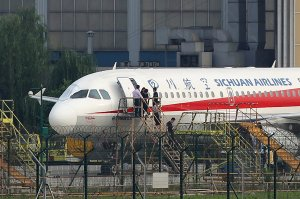"This photo taken on May 14, 2018 shows employees checking a Sichuan Airlines Airbus A319 after an emergency landing, as a broken cockpit window (left) is covered, in Chengdu in China's northwestern Sichuan province. - The pilot who made an emergency landing in southwest China after a broken cockpit window sucked his co-pilot halfway out of the aircraft was hailed as a ""hero"" on May 15 by astonished citizens. All 128 people aboard the Airbus A319 of Sichuan Airlines survived the ordeal. (Credit: AFP/Getty Images)"
