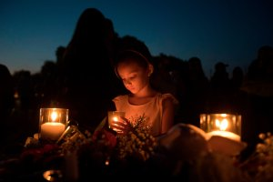Lucretia Martinez, 7, stands before various momentos people have left during a candlelight vigil in Santa Fe, Texas, for the victims of the mass shooting on May 18, 2018. (Credit: AFP / Getty Images)