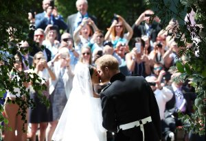 Britain's Prince Harry, Duke of Sussex kisses his wife Meghan, Duchess of Sussex as they leave from the West Door of St George's Chapel, Windsor Castle, in Windsor, on May 19, 2018 after their wedding ceremony. (Credit: DANNY LAWSON/AFP/Getty Images)
