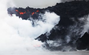 Steam rises as lava enters the Pacific Ocean at dawn, after flowing to the water from a Kilauea volcano fissure, on Hawaii's Big Island on May 22, 2018. (Credit: Mario Tama / Getty Images)
