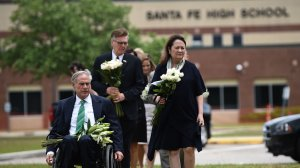 Texas Gov. Greg Abbott, his wife Cecilia Abbott, Lt. Gov. Dan Patrick and other officials bring flowers for a makeshift memorial on the grounds of Santa Fe High School on May, 20, 2018, in Santa Fe, Texas. (Credit: BRENDAN SMIALOWSKI/AFP/Getty Images)