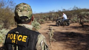 U.S. Immigration and Customs Enforcement tactical officer Kevin Carlos watches as a fellow officer drives off an ATV on Jan. 18, 2011, in the Tohono O'odham Nation, Ariz. (Credit: John Moore/Getty Images)