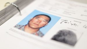 A binder containing the Los Angeles Police Department's files on Koreatown triple-murder suspect, Tai Zhi Cui, shows an image of him alongside his signature. (Credit: Myung J. Chun / Los Angeles Times)