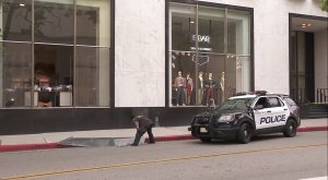 A crime analysts inspects a window that was apparently smashed during a robbery at the Saks Fifth Avenue in Beverly Hills on May 21, 2018. (Credit: KTLA)