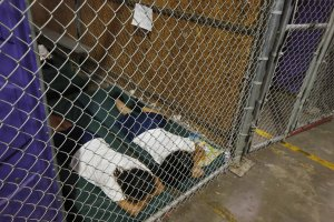 Two female detainees sleep in a holding cell at a U.S. Customs and Border Protection center in Nogales, Arizona, on June 18, 2014. (Credit: Ross D. Franklin / Getty Images via CNN)