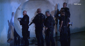 SWAT officers peer into a tunnel where they believe a burglary suspect is hiding in the Valley Village area on May 5, 2018. (Credit: KTLA)