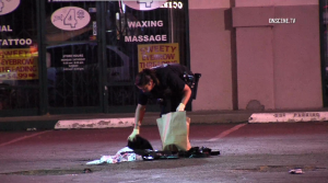 An officer collects evidence at the scene where a security guard was injured in an incident with an unruly patron at a Downey restaurant on May 17, 2018. (Credit: OnScene.TV)