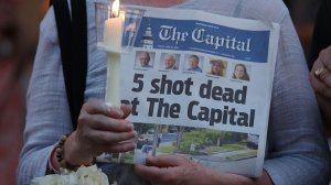 A woman holds an edition of the Capital newspaper during a candlelight vigil on June 29, 2018, to honor the five people who were shot and killed in Annapolis, Maryland. (Credit: Mark Wilson/Getty Images)