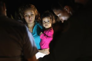 Central American asylum seekers, including a Honduran girl, 2, and her mother, are taken into custody near the U.S.-Mexico border on June 12, 2018, in McAllen, Texas. The group of women and children had rafted across the Rio Grande from Mexico and were detained by U.S. Border Patrol agents before being sent to a processing center for possible separation. (Credit: John Moore/Getty Images)