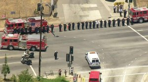 Firefighters salute the van carrying slain Long Beach Fire Department Capt. Dave Rosa as the procession travels to the coroner's office on June 25, 2018. (Credit: KTLA)