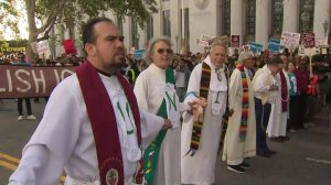 """Clergy members join hands to block Spring Street as they protest the Trump administration's """"zero tolerance"""" immigration policy as Attorney General Jeff Sessions visits Los Angeles on June 26, 2018. (Credit: KTLA)"""