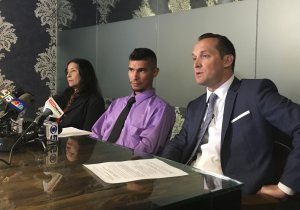 Jose Conde sits between his mother, Rosa Conde, and his attorney, Bret Royle, at a news conference on June 14, 2018, during which he said Mesa police used excessive force during a January arrest. (Credit: Terry Tang/AP via CNN)