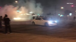 Spectators watch a vehicle perform doughnuts in a Pico Rivera intersection on July 23, 2018. (Credit: RMG News)