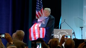 President Donald Trump hugs the American flag after speaking at a National Federation of Independent Business event in Washington on June 19, 2018. (Credit: CNN)