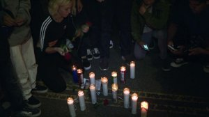 A fan lays roses next to memorial candles in the shape of an X during a vigil for rapper XXXTentacion on Melrose Avenue on June 19, 2018. (Credit: KTLA)